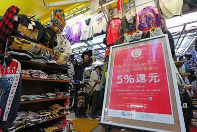 消費増税初日、キャッシュレス決済でポイントが還元されることを知らせるポスターを掲示する洋服店=東京都台東区で