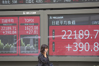 A woman walks by an electronic stock board for a securities firm in Tokyo, on Oct. 15, 2019. (AP Photo/Koji Sasahara)