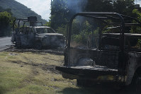Charred trucks that belong to the Michoacan state police stand on the roadside after they were attacked in El Aguaje, Mexico, Monday, Oct. 14, 2019. (AP Photo/Armando Solis)