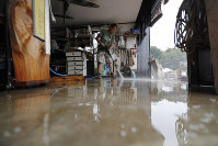 A volunteer helps clean up, on Oct. 14, 2019, in Kawagoe City, Japan. (AP Photo/Eugene Hoshiko)