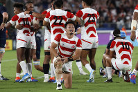 Japan's Kenki Fukuoka and teammates celebrate after winning over Scotland in the Rugby World Cup Pool A game at International Stadium in Yokohama, Japan, on Oct. 13, 2019. (AP Photo/Eugene Hoshiko)