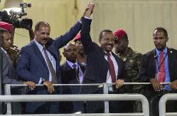 戦争状態の終結を祝って開かれたコンサートで、エリトリアのイサイアス・アフェウェルキ大統領(左端)と手を取り合うエチオピアのアビー・アハメド首相=2018年7月15日、AP