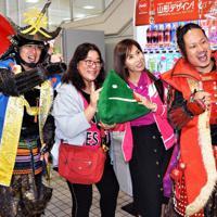 出迎えた「やまがた愛の武将隊」と記念撮影する台湾からのツアー客=庄内空港で