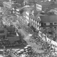楠港(当時)に到着し、人波の中を進む聖火=大分県別府市で1964年9月12日、本社ヘリ「かもめ号」から撮影