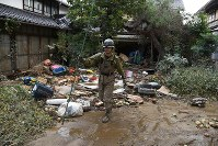 A Self-Defense Force member searches for missing people in a residential area that was flooded when a bank of the Chikuma River burst due to heavy rain caused by Typhoon Hagibis, in the central Japan city of Nagano on Oct. 15, 2019. There was a report that a dead body had been found in the yard of a house in the area on that morning. (Mainichi/Hiroshi Maruyama)