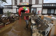 Staff members clean up their restaurant, which was flooded after a bank of the Chikuma River burst due to heavy rain caused by Typhoon Hagibis, in the central Japan city of Nagano on Oct. 15, 2019. (Mainichi/Hiroshi Maruyama)