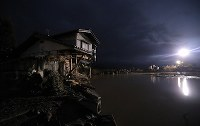 A house which was destroyed due to the flooding of the Chikuma River caused by Typhoon Hagibis is seen in the dark in the central Japan city of Nagano on Oct. 15, 2019. A burst river bank is seen in the background. (Mainichi/Yuki Miyatake)
