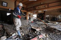 A man cleans up his relative's house that was flooded after a bank of the Chikuma River burst due to heavy rain caused by Typhoon Hagibis, in the central Japan city of Nagano on Oct. 15, 2019. (Mainichi/Yuki Miyatake)
