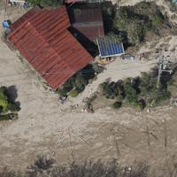宮城県丸森町中心部への道が断たれ孤立した集落では、上空から見えるように枝などを使って「水 食料」の文字が書かれていた=同町で10月15日午後0時32分、本社ヘリから
