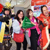 出迎えた「やまがた愛の武将隊」と記念撮影する台湾からのツアー客=庄内空港で2019年10月15日、高橋不二彦撮影