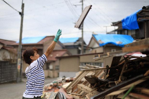 台風15号の強風で吹き飛ばされたがれきを片付ける女性。多くの住宅の屋根はブルーシートに覆われていた=千葉県鋸南町大帷子で2019年9月13日