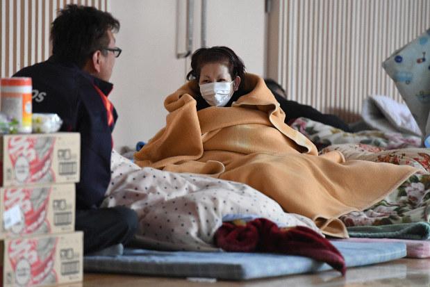 2016年の熊本地震で被災し、避難所で毛布や布団で寒さをしのぐ人たち=熊本県南阿蘇村で同年4月19日
