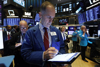 In this Oct. 8, 2019, file photo trader Mark Puetzer, center, works on the floor of the New York Stock Exchange. (AP Photo/Richard Drew)