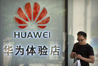In this May 29, 2019, file photo, a man uses his smartphone outside of a shop selling Huawei products at a shopping mall in Beijing. (AP Photo/Mark Schiefelbein)