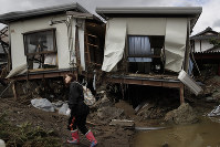 A woman surveys her home after it was destroyed by Typhoon Hagibis in Nagano, Japan, on Oct. 15, 2019. (AP Photo/Jae C. Hong)