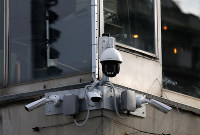 In this Sept. 25, 2019 photo, high-tech video cameras hang from an office building in downtown Belgrade, Serbia. (AP Photo/Darko Vojinovic)