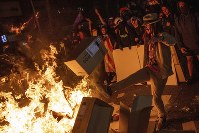 Protesters throw cartons to a burning barricade during clashes with police in Barcelona, Spain, on Oct. 15, 2019. (AP Photo/Bernat Armangue)
