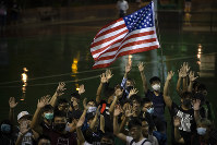 A demonstrator holds a U.S. flag during a rally at the Southorn Playground in Hong Kong, on Oct. 15, 2019. (AP Photo/Mark Schiefelbein)