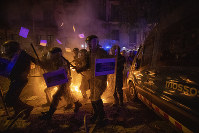 Policemen in riot gear move past a burning barricade during clashes with protestors in Barcelona, Spain, on Oct. 15, 2019. (AP Photo/Emilio Morenatti)