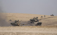 Turkish tanks and troops stationed near the Syrian town of Manbij in Syria, on Oct. 15, 2019. (Ugur Can/DHA via AP)