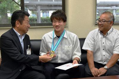 藤田教育長(左端)に笑顔で優勝したメダルを見せる山本さん(中央)=滋賀県東近江市役所で、蓮見新也撮影