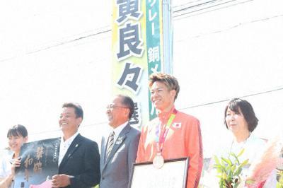 懸垂幕の前で記念撮影に応じる白石選手(右から2人目)と母ひとみさん(右端)