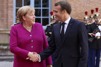 French President Emmanuel Macron welcomes German Chancellor Angela Merkel in the government building of Toulouse, southwestern France, on Oct.16, 2019. (AP Photo/Frederic Scheiber)