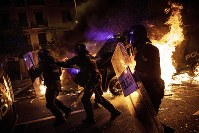Police officers run as a police van drives over a burning barricade during clashes between protestors and police in Barcelona, Spain, on Oct. 16, 2019. (AP Photo/Bernat Armangue)