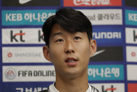 South Korean national soccer team player Son Heung-min answers reporter's question upon his arrival after the soccer match against North Korea, at Incheon International Airport in Incheon, South Korea, on Oct. 17, 2019. (AP Photo/Lee Jin-man)