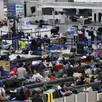 出発ロビーでベンチや寝袋などを使って横になる旅客=成田空港で9月10日午前4時16分、藤井達也撮影