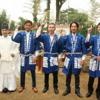 手渡された法被を着て気合を入れる木山神宮氏子青年会のメンバーと矢田祢宜(左)。中央は北村氏子青年会長