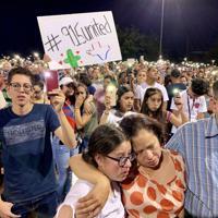 銃乱射事件の翌日に開かれた追悼集会で明かりを掲げ、犠牲者のために祈る住民たち。団結し、人種差別に負けない決意を示した=米南部テキサス州エルパソで2019年8月4日、福永方人撮影