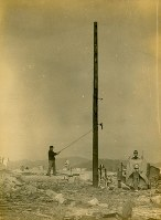 An examination of a utility pole is seen underway in Hiroshima's Naka Ward, after the atomic bombing of the city, in this photo taken by Kiyoshi Kanai and Toshio Maeda.