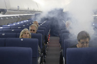 FAA employees participate in a demonstration of an airline cabin filling with smoke, in a simulator at the FAA Civil Aerospace Medical Institute in the Mike Monroney Aeronautical Center on Oct. 17, 2019, in Oklahoma City. (AP Photo/Sue Ogrocki)