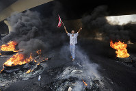 An anti-government protester makes victory sign, as he holds a Lebanese national flag and walks around tires on fire to block a road during a protest against government's plans to impose new taxes in Beirut, Lebanon, on Oct. 18, 2019. (AP Photo/Hassan Ammar)