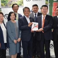 片峯市長(中央)に寄付の目録を手渡した林田自治会長(右から2人目)と実行委員会のメンバー