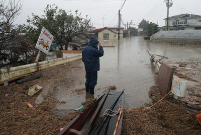 台風19号で吉田川が氾濫して浸水し、1週間がたった今も水が引かない住宅地を見つめる男性。雨の影響で午前中は自宅に向かうのをやめた=宮城県大崎市鹿島台で2019年10月19日午前8時58分、和田大典撮影