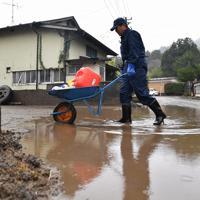 雨が降る中水くみから帰宅した横山祐一さん=宮城県丸森町で2019年10月19日午前9時5分、猪飼健史撮影