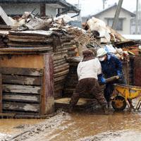 降りしきる雨の中、浸水した畳などを廃棄する人たち=長野市津野で2019年10月19日午後2時2分、小川昌宏撮影