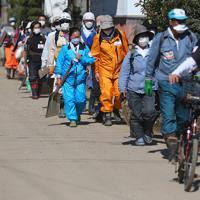 並んでスコップなどを手に、作業に向かうボランティアたち=長野市赤沼で2019年10月19日午前11時59分、小川昌宏撮影