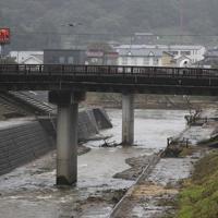 安達太良川にかかる橋の上を傘を差して歩く人=福島県本宮市で2019年10月19日午前8時、吉田航太撮影