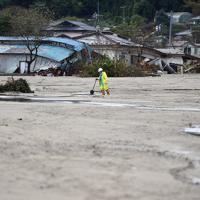 一面土砂で覆われた被災現場を歩く男性=宮城県丸森町で2019年10月19日午後3時43分、猪飼健史撮影
