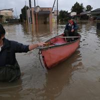 台風19号の影響で吉田川が氾濫し、浸水した米農家の八木秀敏さん(69)=右=宅では1週間たった今も水が完全には引いていない。八木さんは福島県郡山市から駆けつけた長男秀一さんと雨足が弱まった午後、水位が1・5メートルほどになった場所を船でぬけて、家具などが散乱する家や倉庫の片づけをした=宮城県大崎市で2019年10月19日午後4時29分、和田大典撮影