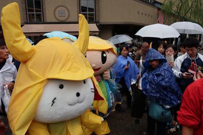 雨の中、レインコートを着て愛嬌(あいきょう)を振りまく滋賀県彦根市の「ひこにゃん」=滋賀県彦根市本町1で2019年10月19日午前9時18分、西村浩一撮影