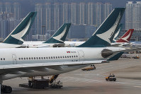 In this Aug. 12, 2019, file photo, ground crew drive past Cathay Pacific Airways planes park at the Hong Kong International Airport. (AP Photo/Vincent Thian)