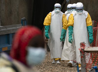 In this July 16, 2019 file photo, health workers dressed in protective gear begin their shift at an Ebola treatment center in Beni, Congo DRC. (AP Photo/Jerome Delay)