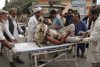 A wounded man is brought by stretcher into a hospital after a mortar was fired by insurgents in Haskamena district of Jalalabad east of Kabul, Afghanistan, on Oct. 18, 2019. (AP Photo/Wali Sabawoon)