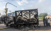 A burnt-out truck used by gunmen smolders on an intersection, a day after street battles between gunmen and security forces in Culiacan, Mexico, on Oct. 18, 2019. (AP Photo/Augusto Zurita)