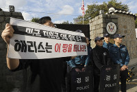 In this Oct. 18, 2019, photo, a college student holds a banner in front of the U.S. ambassador's residence in Seoul, South Korea. (Chun Jin-hwan/Newsis via AP)