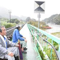 JRの鉄橋に座る集落の住民。石井通さん(手前)は「家の中にいるばかりで頭がおかしくなる。気晴らしにここへ来た」と話す=福島県矢祭町で2019年10月19日午前10時1分、古川幸奈撮影
